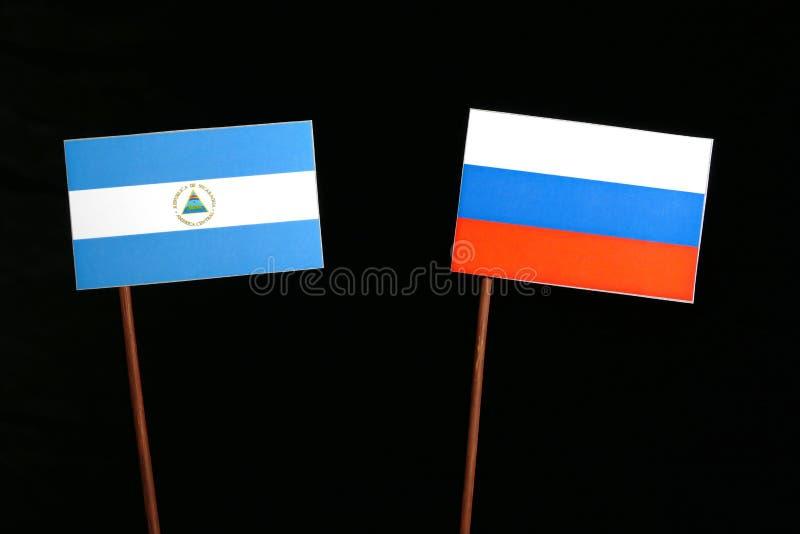 Nicaraguan vlag met Russische vlag op zwarte stock afbeeldingen