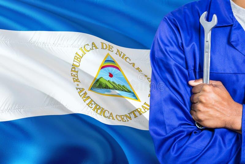 Nicaraguan Werktuigkundige in blauwe eenvormig houdt moersleutel tegen golvende de vlagachtergrond van Nicaragua Gekruiste wapens stock foto