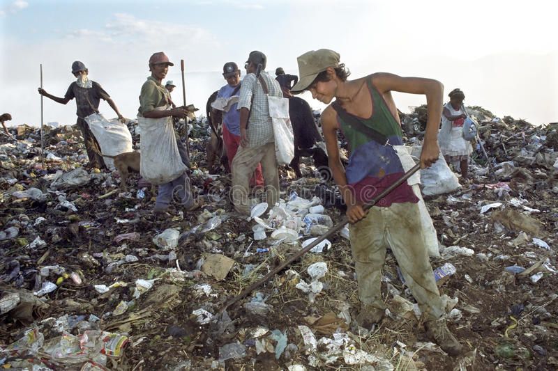 Nicaraguans working in garbage dump, Managua. Nicaragua, capital, city Managua: men, woman and a boy stand to collect recyclables from the garbage at the stock image