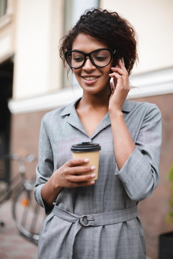 Nice African American girl in glasses standing on street and talking on her cellphone with coffee. Lady with dark curly. Nice African American girl in glasses stock image