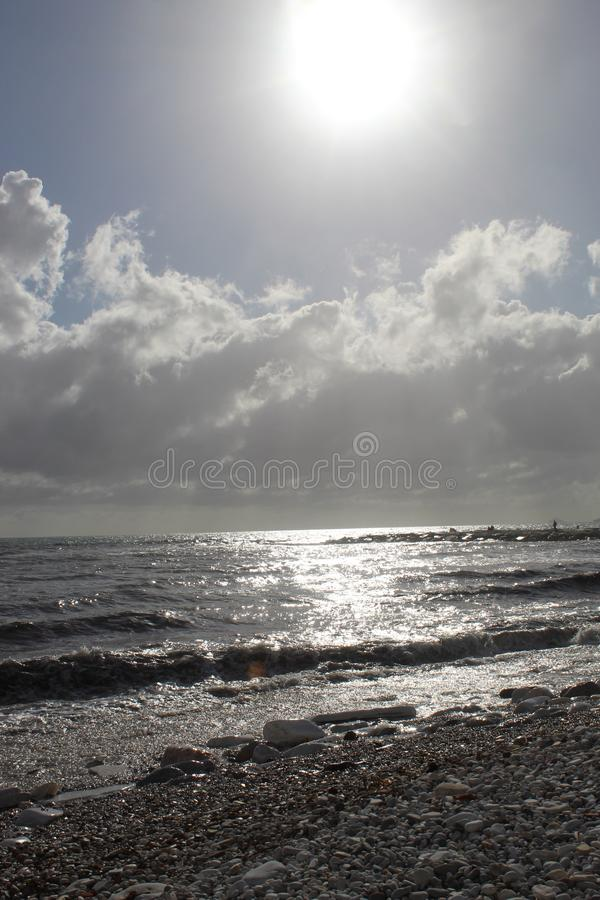 A nice afternoon at the beach in Tuscany, Italy. It was a sunny day at the beach. You could see the high  waves in the water.  There are rocks in the ocean royalty free stock photo
