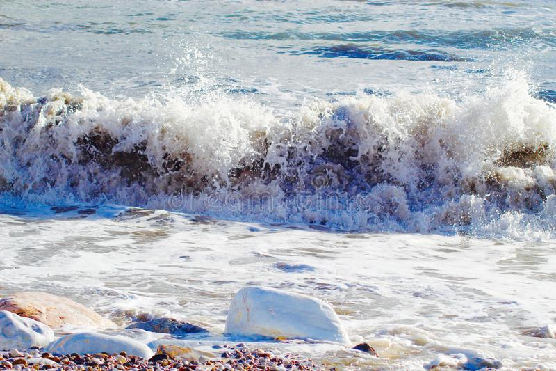 A nice afternoon at the beach in Tuscany, Italy. It was a sunny day at the beach. You could see the high  waves in the water.  There are rocks in the ocean royalty free stock photos