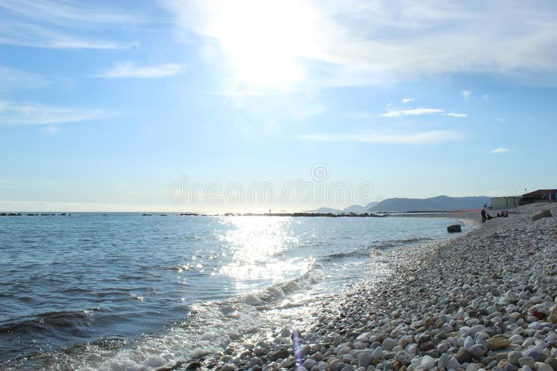 A nice afternoon at the beach in Tuscany, Italy. It was a sunny day at the beach. You could see the high  waves in the water.  There are rocks in the ocean stock photography