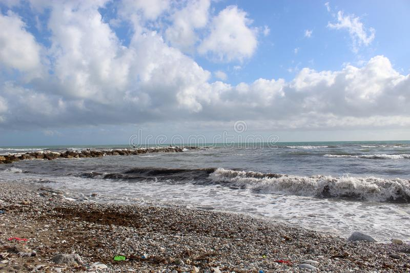 A nice afternoon at the beach in Tuscany, Italy. It was a sunny day at the beach. You could see the high  waves in the water.  There are rocks in the ocean stock images