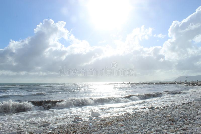 A nice afternoon at the beach in Tuscany, Italy. It was a sunny day at the beach. You could see the high  waves in the water.  There are rocks in the ocean stock photos