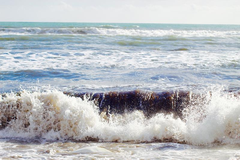 A nice afternoon at the beach in Tuscany, Italy. It was a sunny day at the beach. You could see the high  waves in the water.  There are rocks in the ocean royalty free stock photography