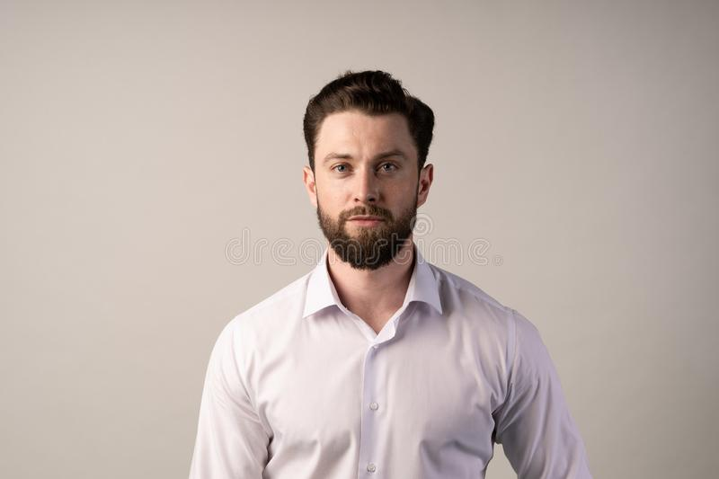 Nice american guy with a beard on a white background, outside, in shirt. Cool beard and mustashe. Nice american guy with a beard on a white background, outside stock image