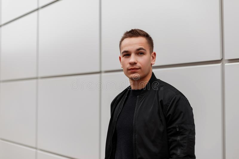 Nice american handsome young man in a fashionable black jacket in a T-shirt posing standing near a modern building outdoors. stock image