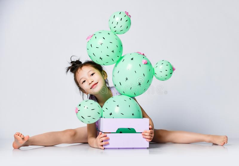 Nice asian girl take the splits behind the box with cactus balloon in it, peeks out and smiles sweetly royalty free stock photography