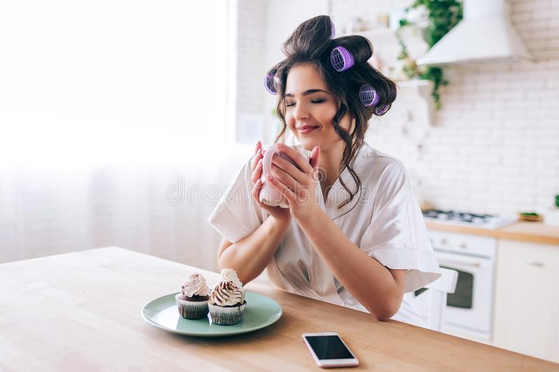 Nice attractive beautiful young woman in kitchen. Hold cup in hands and dream. Eyes closed. Pancakes on plate. Phone on royalty free stock photography