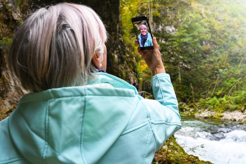 Nice attractive elderly mature woman with shiny grey hair taking photos and selfies outdoor royalty free stock photography