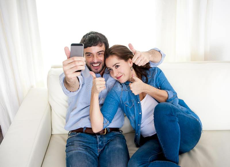 Nice attractive young couple sitting together in sofa couch taking selfie photo with mobile phone. Sitting on couch celebrating love and new home, flat or house royalty free stock images