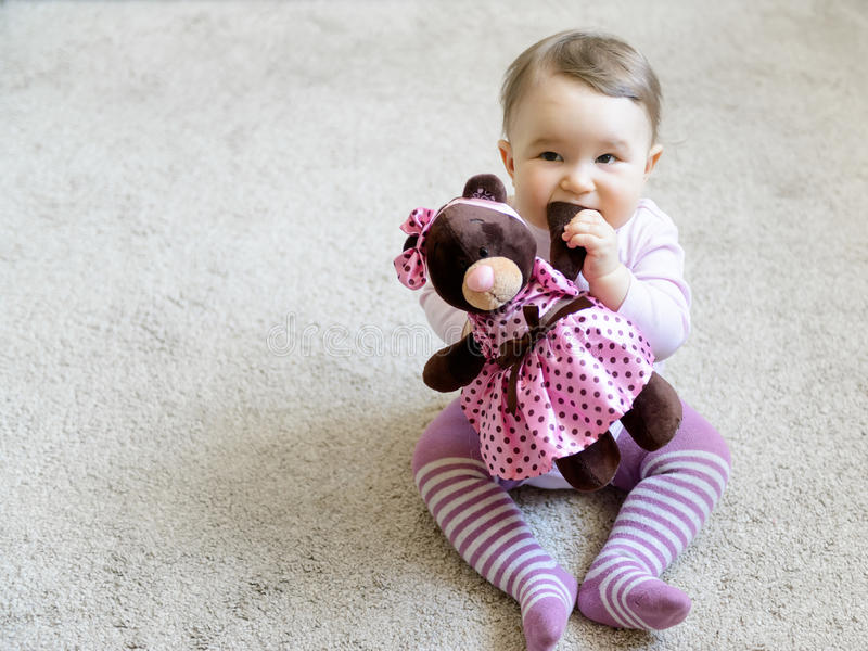 Nice baby girl bites the paw of the toy bear. Pretty baby girl bites the paw of the toy bear royalty free stock photography