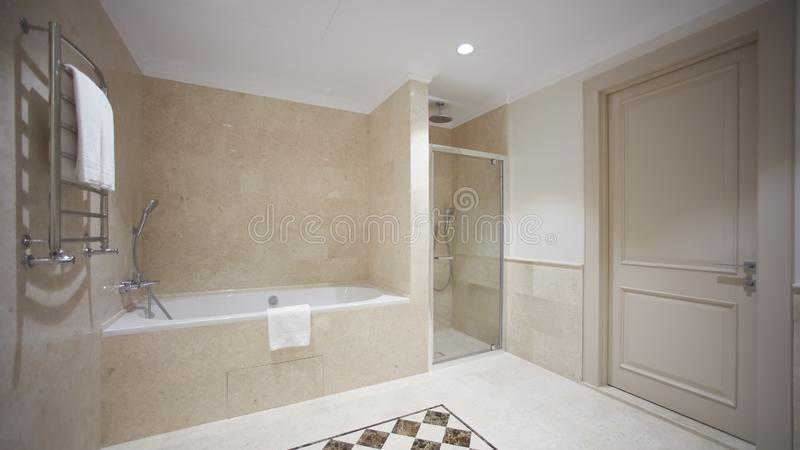 Nice bathroom in a modern style with gray tiled walls. There is a white bath with a glass partition, shower, mirrors. Light sink, toilet and a bidet, luminous royalty free stock photo