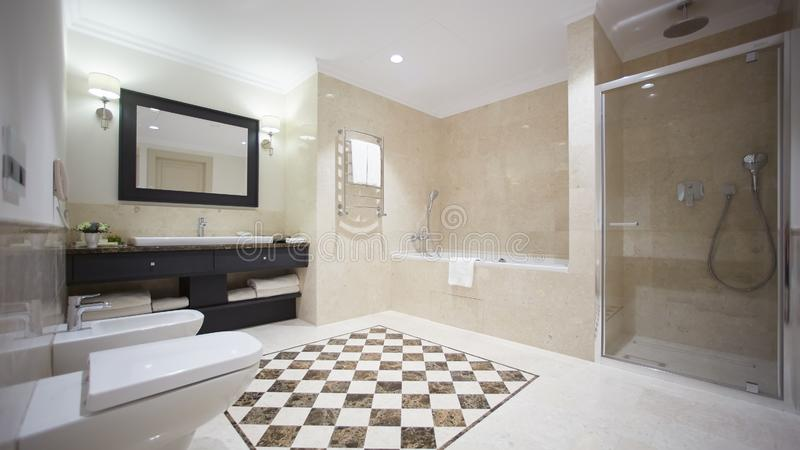 Nice bathroom in a modern style with gray tiled walls. There is a white bath with a glass partition, shower, mirrors. Light sink, toilet and a bidet, luminous royalty free stock image