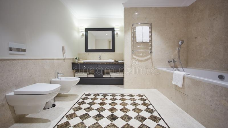 Nice bathroom in a modern style with gray tiled walls. There is a white bath with a glass partition, shower, mirrors. Light sink, toilet and a bidet, luminous stock images