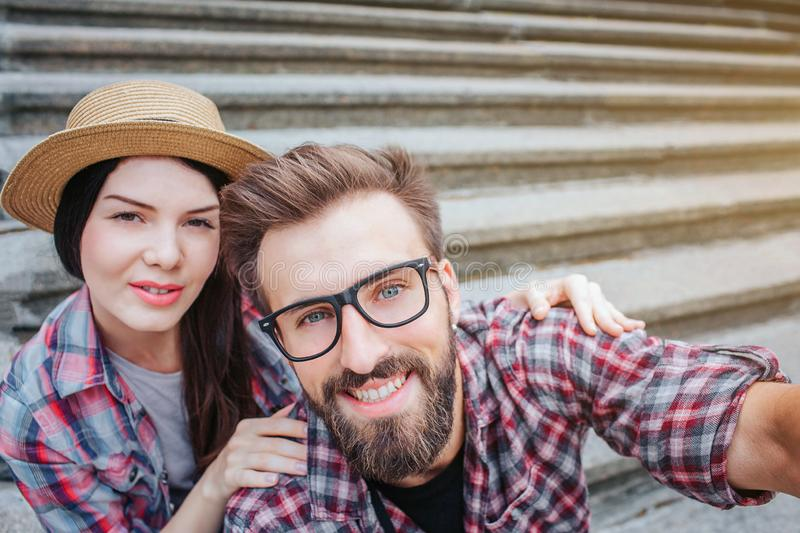 Nice bearded man and positive young woman sit on stairs and pose. He holds camera. They look at it. Tourists have rest. royalty free stock photo