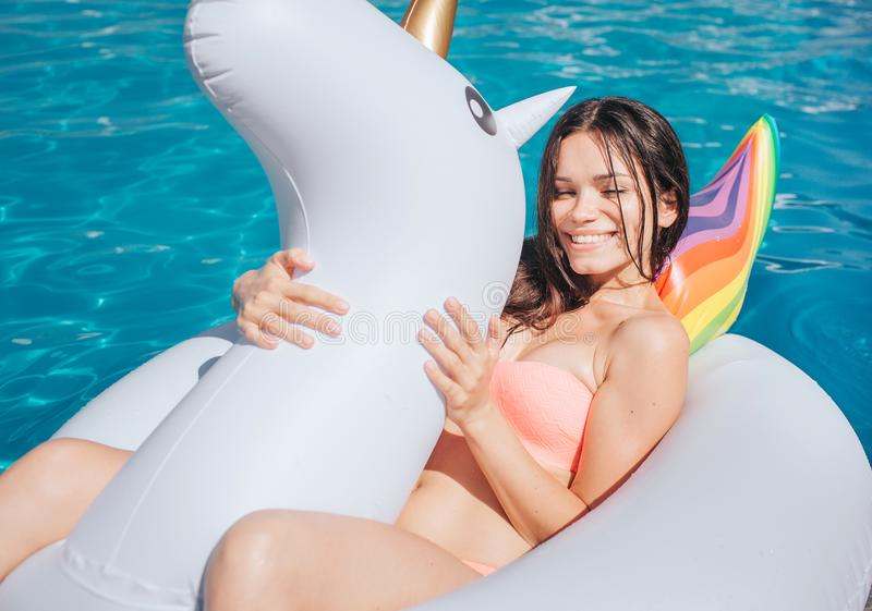 Nice and beautiful girl is lying on air mattress. It has shape of unicorn. Girl holds it with both hands and smiles. She stock images