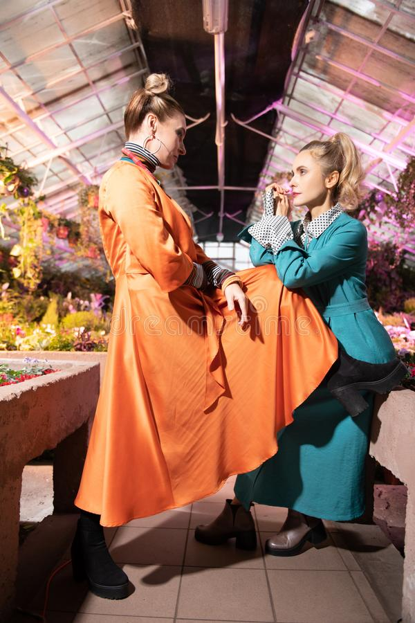 Nice beautiful women looking at each other. Young models. Nice beautiful women looking at each other while being in the greenhouse stock images