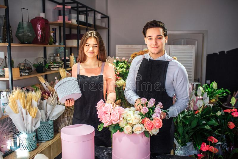 Nice and beautiful young florists look on camera. They stand at table Young woman hold small grey box. Guy touch flowers royalty free stock images