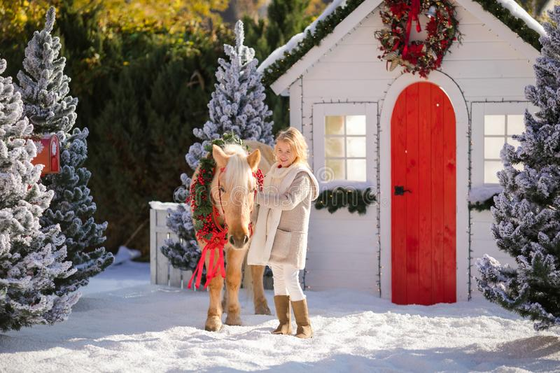 Nice blonde curly child and adorable pony with festive wreath near the small wooden house and snow-covered trees. royalty free stock image