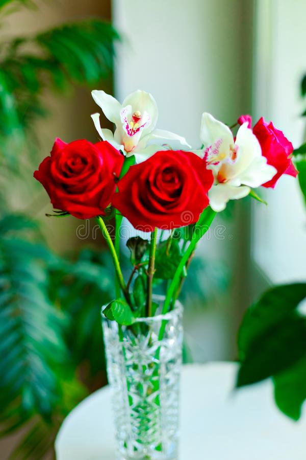 Nice bouquet from red roses and white orchids in vase  on white background royalty free stock photos