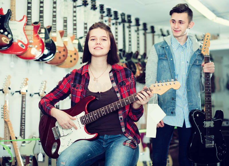 Nice boy and girl teenagers examining electric guitars stock images