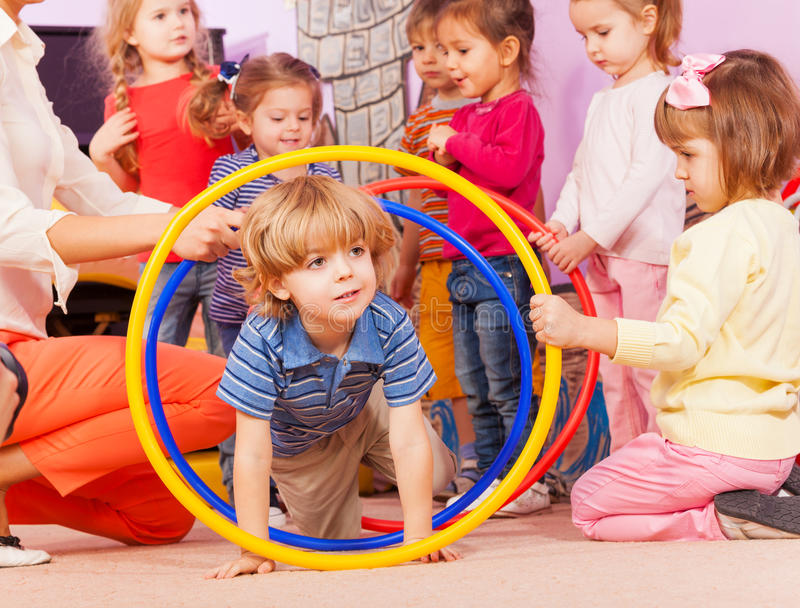 Nice boy play with hoops in kindergarten goup. Cute boy play with boys and girls active game going though hoops in kindergarten stock image