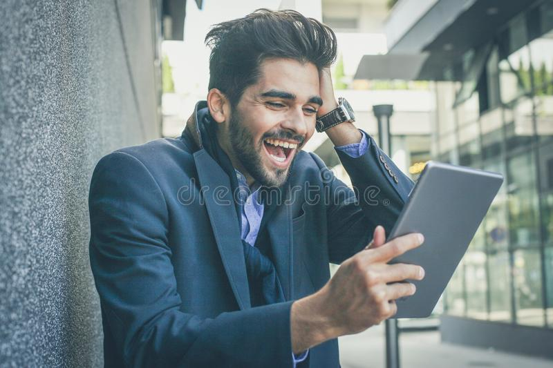 Nice business news keeps me going. Business man using digital tablet on city street. Man receiving good news royalty free stock photo