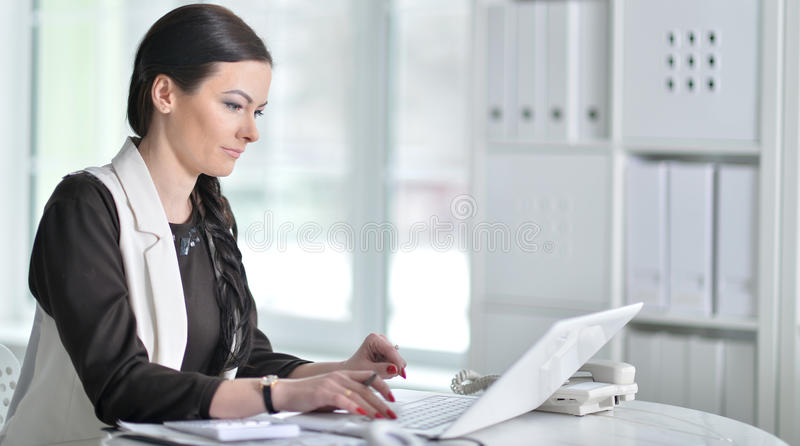Nice business woman sitting with laptop royalty free stock photo