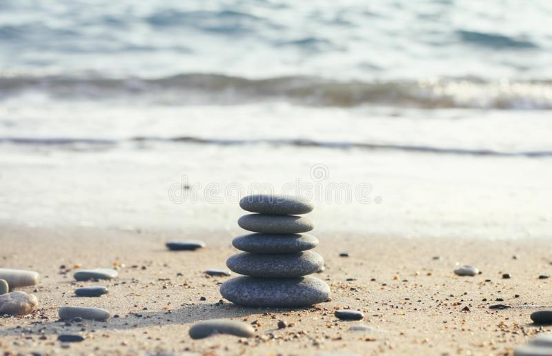 Zen pyramid of spa stones on the blurred sea background. Sand on a beach. Sea shores. Water waves texture. Left side of photo. Pla stock photo