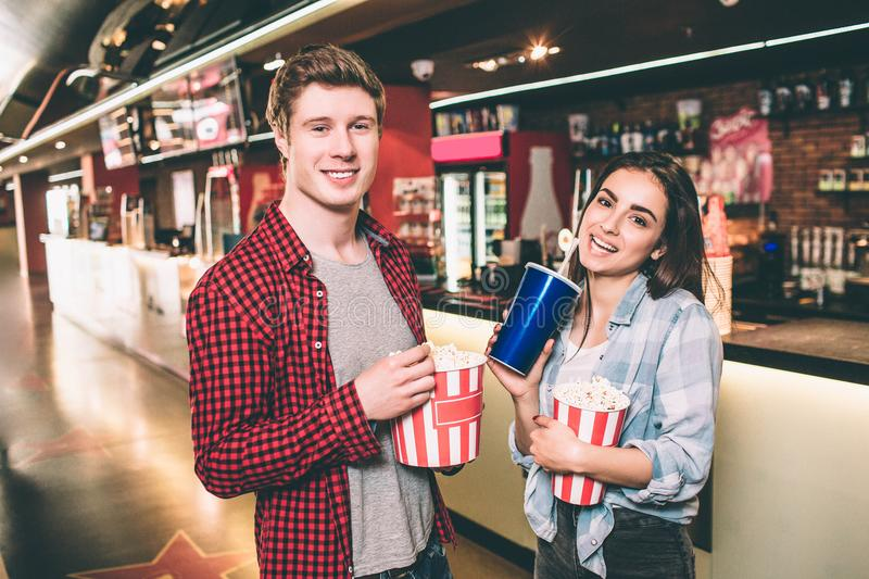 Nice and cheerful couple are standing in hall and holding two baskets of popcorn. She is holding a cup of coke as well royalty free stock photos