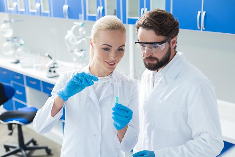 Nice cheerful woman holding test tubes royalty free stock images