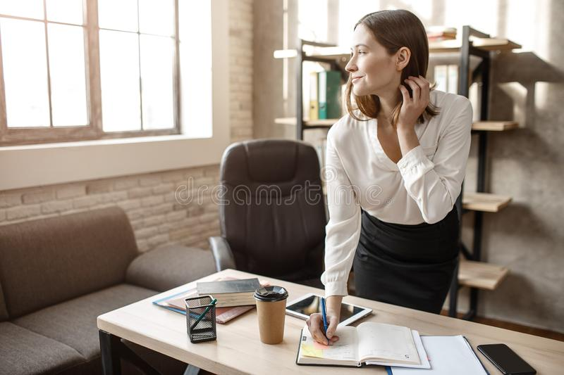 Nice cheerful young businesswoman look at window and smile. She stand in room and write in notebook. stock images