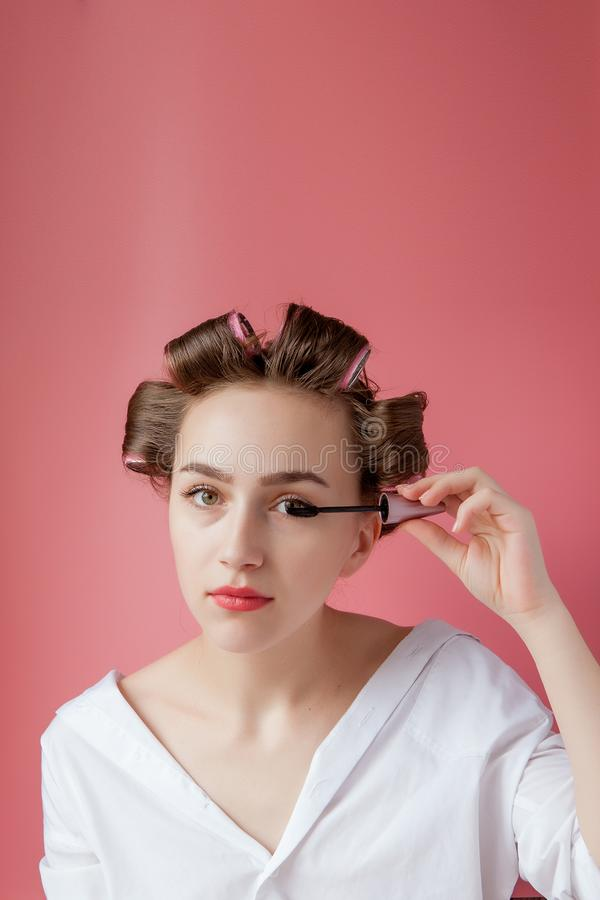 Nice cheerful young the girl in the curler paints an eyebrow on pink background royalty free stock image