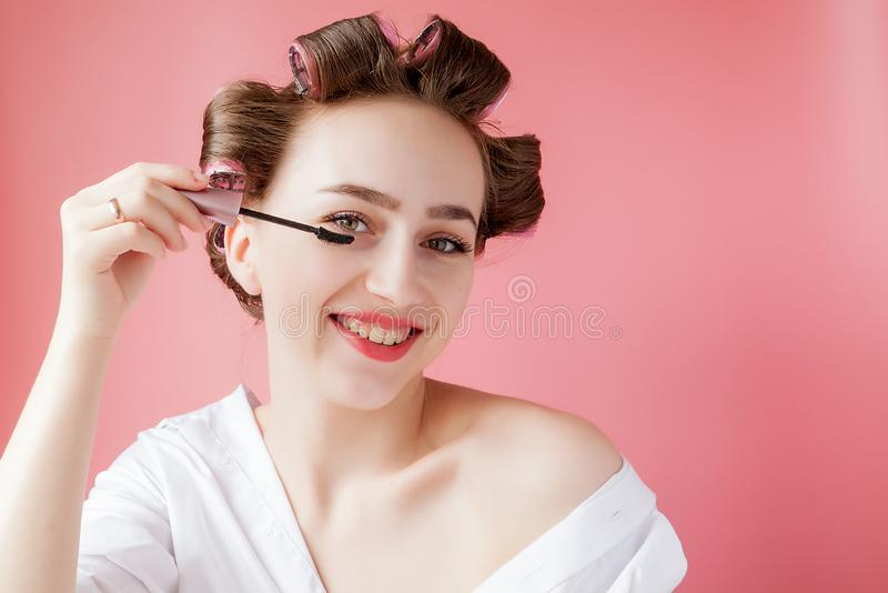 Nice cheerful young the girl in the curler paints an eyebrow on pink background royalty free stock images