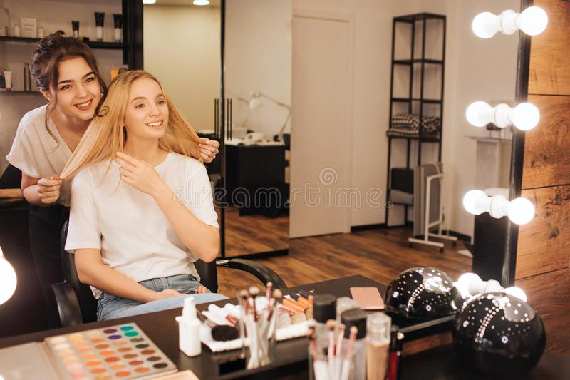 Nice cheerful young make up artist stand behind blonde model and smile to her in beauty room. she hold her hair and look. Into mirror. Client point on hair royalty free stock images