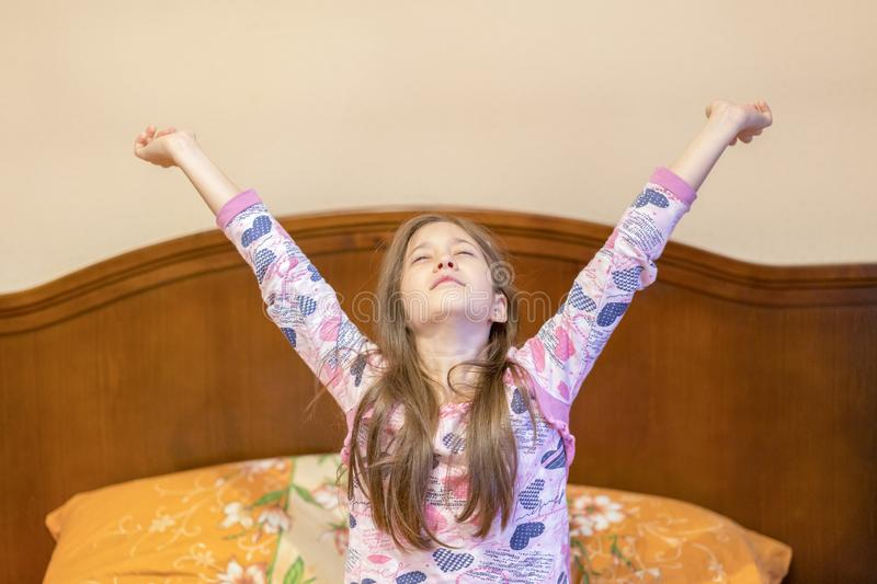 A nice child girl enjoys sunny morning. Good morning at home. Child girl wakes up from sleep. Little girl stretching in bed at. Home. Time to sleep royalty free stock image