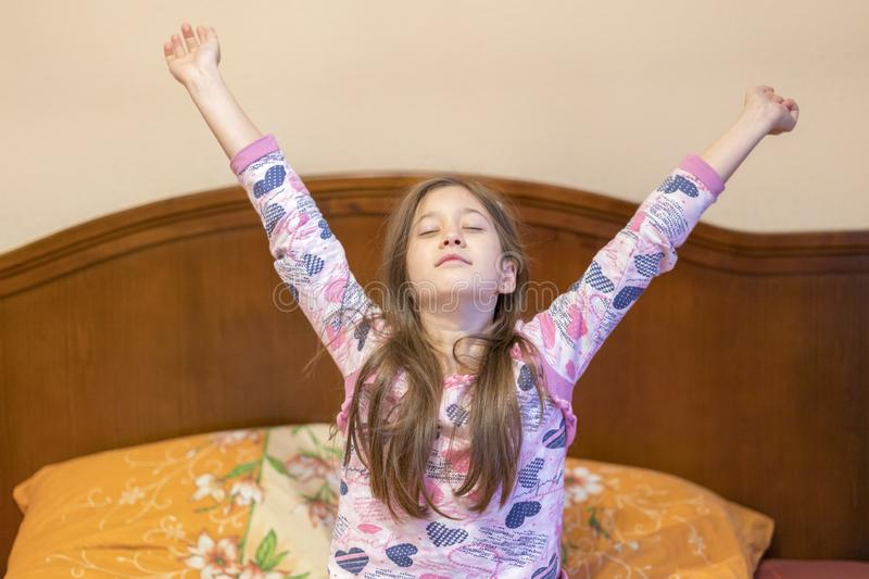 A nice child girl enjoys sunny morning. Good morning at home. Child girl wakes up from sleep. Little girl stretching in bed at. Home. Time to sleep royalty free stock images