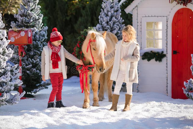 Nice children and adorable pony with festive wreath near the small wooden house and snow-covered trees. New Year and Christmas tim. E outdoor royalty free stock images