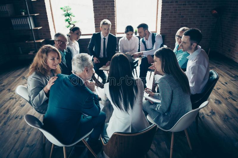 Nice classy elegant stylish attractive focused concentrated specialists sitting on chairs discussing financial corporate. Conference at modern industrial loft stock photo