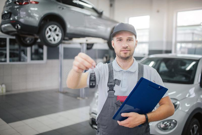 Nice and confident man stands and looks on camera. He holds car keys and plastic folder with documents. There are tow royalty free stock photo