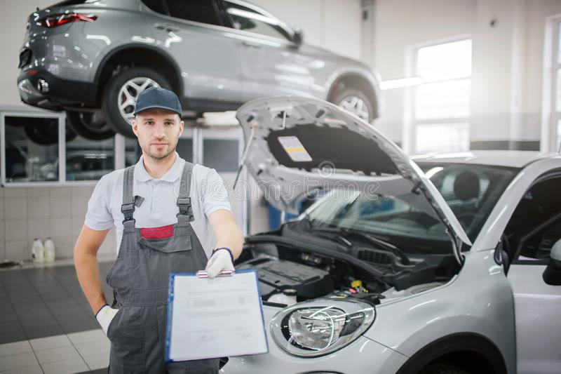 Nice and confident young man stands at car and looks on camera. He holds plastic folder with documents on it. One hand royalty free stock photo