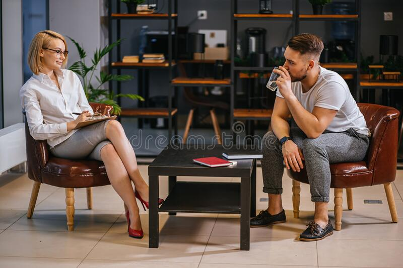 Nice conversation between patient and psychologist. Young men patient and women psychologist have nice conversation, men looks at psychologist with confidence stock photography