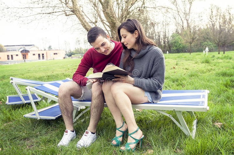 Nice couple relax on deckchair reading book and tablet. Outdoors royalty free stock image