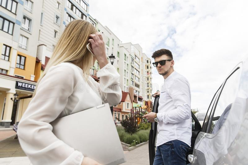 Nice couple are standing together outside on street. Guy is leaning on car`s door. He wears glasses. Girl looks at the guy, and h royalty free stock photography