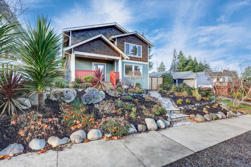 Nice Craftsman home exterior on blue sky background. Well kept frontyard with natural stone landscape design. Northwest, USA royalty free stock photo