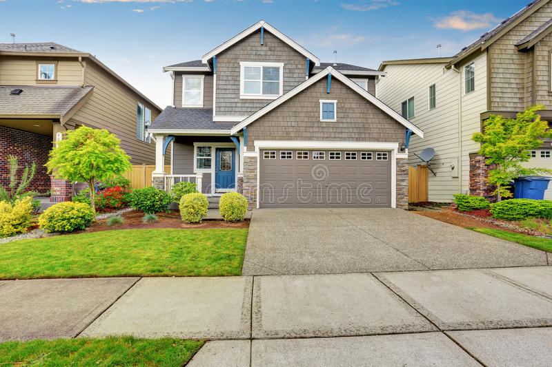 Nice curb appeal of two level house mocha exterior paint and concrete driveway stock image for Exterior concrete driveway paint