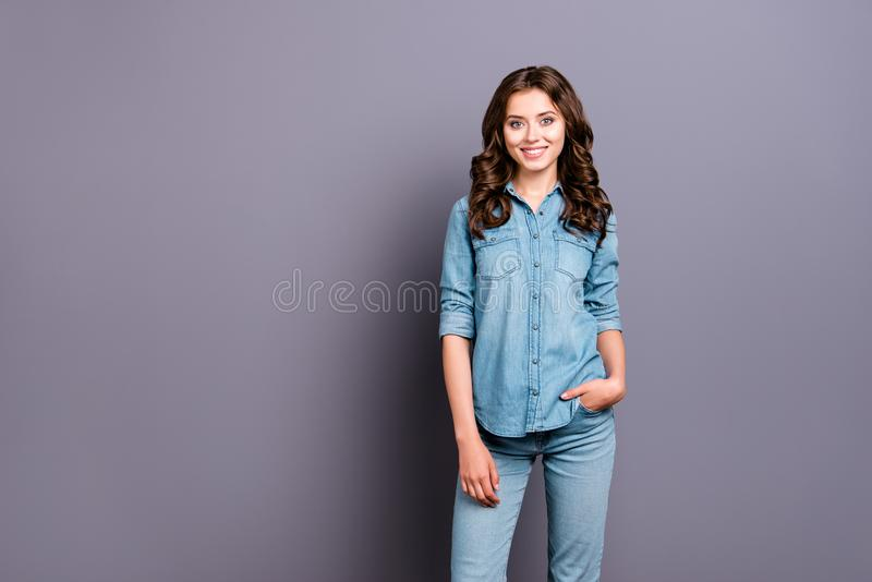 Nice cute cheerful attractive adorable girl with wavy hair in ca. Sual denim shirt and jeans, holding hand in pocket isolated over grey background royalty free stock photography