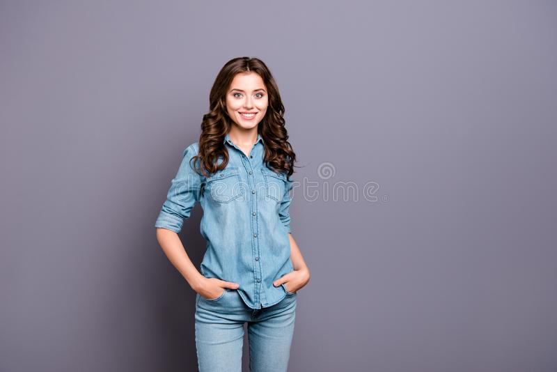 Nice cute cheerful attractive adorable girl with wavy hair in ca. Sual blue denim shirt and jeans, holding hands in pockets, isolated over grey background royalty free stock images